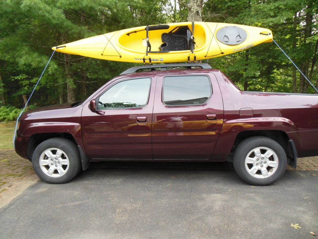 The 12-foot Pungo atop the Packem racks. Note that the open side is facing out. I now have the racks turned around with the short open side facing inward. I found this easier to manage. Since  I never dismount the kayak from the side it does not make any difference.