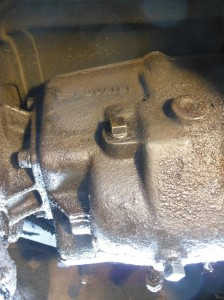 This is a view of the transmission from the right (passenger) side of the car. The square bolt head at the top is the filler plug. Remove that, squeeze in hydraulic fluid until it leaks out. The only way I could reach this was by lifting the car.