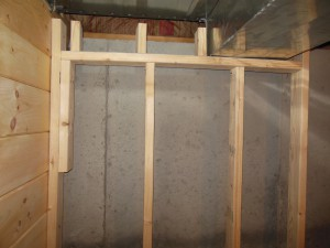 The back wall is against the foundation. It also surrounds the heating ducts at the top.